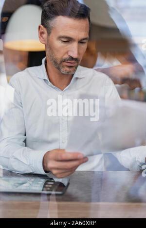 Businessman derrière la vitre dans un café lecture papers Banque D'Images