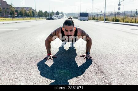 Jeune homme faire poussez se lève sur une route