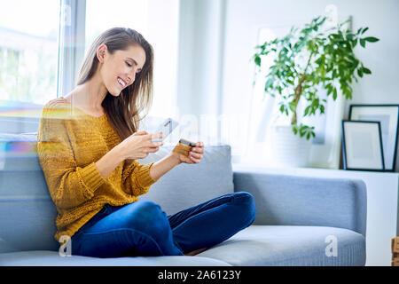 Belle femme heureuse de payer en ligne avec carte de crédit et smartphone while sitting on sofa