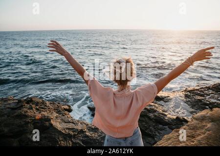 Vue arrière du jeune femme de la mer avec les bras levés, Sunset Cliffs, San Diego, California, USA