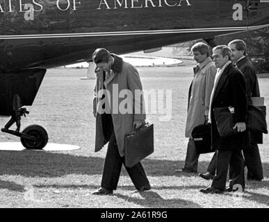 Washington DC., USA, le 28 janvier 1984, le président Ronald Reagan de promenades le bureau ovale à la Maison Blanche pelouse Sud à bord d'un marin pour un vol à Camp David dans le Maryland les montagnes. Agissant Secrétaire de presse de la Maison Blanche Larry Speakes (3e à partir de la droite) et d'autres membres du personnel à pied avec Reagan Banque D'Images