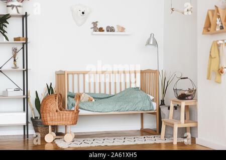 Chambre bébé lit en bois confortable avec intérieur en osier et poussette