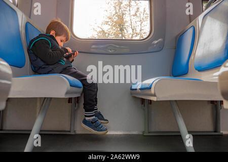 Garçon avec un téléphone mobile assis en train. Les enfants et les technologies. Jeune garçon joue une partie sur le téléphone tout en restant assis dans le train. La qualité de connexion internet. Jeune voyageur Voyages avec la carte électronique