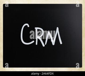 Le mot 'CRM' à la main avec craie blanche sur un tableau noir Banque D'Images