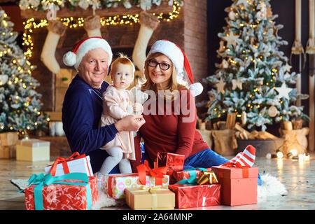 Les grands-parents et petite fille dans la maison à Noël. Banque D'Images