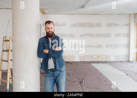 Jeune homme barbu debout les bras croisés appuyé contre un pilier dans une nouvelle construction à la maison inachevée à l'appareil photo de manière réfléchie Banque D'Images