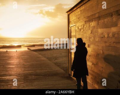 Vue arrière de la femme sur la promenade de la plage au coucher du soleil Banque D'Images