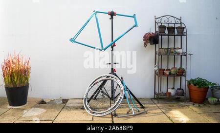Vélo rétro bleu en avant d'un mur blanc prêt pour la restauration Banque D'Images