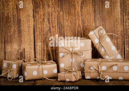 Boîtes cadeaux ou présent enveloppé dans du papier craft sur fond de bois. Copier l'espace. Banque D'Images