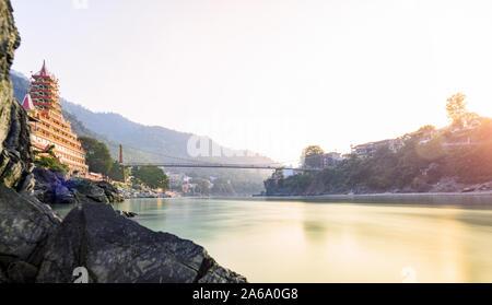 Vue imprenable sur la berge de la rivière Ganga avec le Lakshman Jhula bridge et Tera (Trimbakeshwar Temple Manzil) au cours d'un beau coucher du soleil. Banque D'Images
