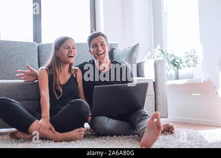 Close up. jeune couple aborder quelque chose assis sur le canapé . Banque D'Images