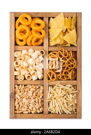 Diverses collations dans vintage boîte en bois isolé sur blanc. Onion rings,nachos, cacahuètes salées avec des pommes de terre coupées et les bretzels. Convient pour la bière et fizzy Banque D'Images