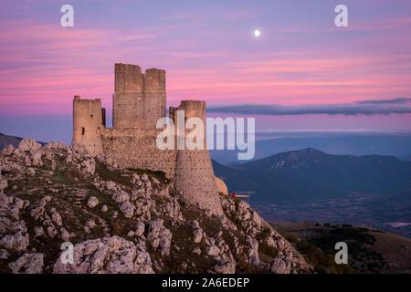 Ruines du château médiéval de Rocca Calascio après le coucher du soleil et de la lune avec l'augmentation des paysages de montagne et ciel colorés en arrière-plan, les Abruzzes, Italie Banque D'Images