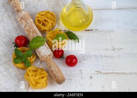Ingrédients pour les pâtes italiennes. Les pâtes, fromage, basilic, tomates cerises, de l'huile d'olive, l'oeuf, l'oeuf. Sur un fond clair. Copier l'espace. Banque D'Images