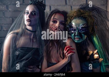 Trois femmes dans un carnaval costumes de vampire bride, mutant sanglant et sorcière. Halloween concept. Banque D'Images