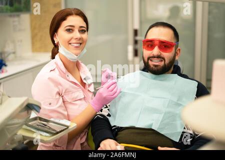 Jeune femme médecin dentiste et patient smiling at camera à la clinique dentaire. Lunettes de sécurité pour le patient. Le médecin personnel de protection en equi