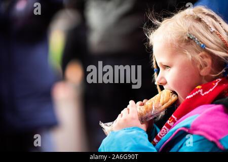 Une jolie petite fille bénéficie d'une saucisse chaude à un match de football de Stoke City FC, BET 365 Stadium