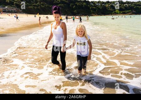 Mère et fille heureux, souriant, le canotage, la marche dans la mer à la magnifique ville de St Ives en Cornouailles, Royaume-Uni, le Carbis Bay magnifique Banque D'Images