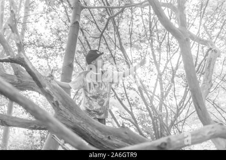Un petit garçon assis dans un champ de maïs portant un chapeau de base-ball, tandis que dehors à jouer avec des amis Banque D'Images