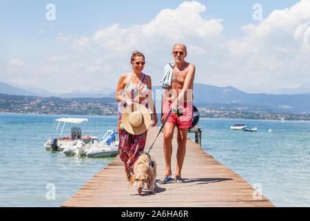 Couple mature en maillot de marcher avec un chien sur le quai d'une station. Concept de belles personnes s'amusant en été Banque D'Images
