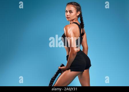 La sportive impressionnante à dos pendant l'entraînement avec corde bataille. close up retour voir photo. isolated blue background, studio shot Banque D'Images