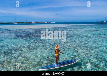Drone aérien bird's eye view photo de jeune femme pratiquant ou sup paddle board in tropical Caribbean sapphire crystal clear eaux calmes