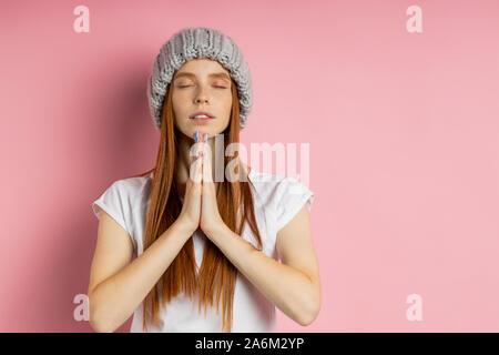 Jeune femme rousse calme aux yeux clos la pratique du yoga, en gardant les paumes ensemble, prier pour la paix et l'amour, la méditation, le port d'un chapeau tricoté gris Banque D'Images