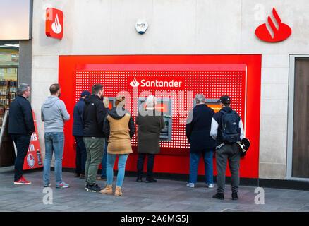 Les gens faire la queue pour utiliser des machines à la Banque Santander à Liverpool