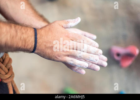 Close up of man grimpeur dans les mains de revêtement en poudre de magnésium et de craie prépare à escalader un mur de pierre d'entraînement à l'extérieur d'entraînement . Banque D'Images