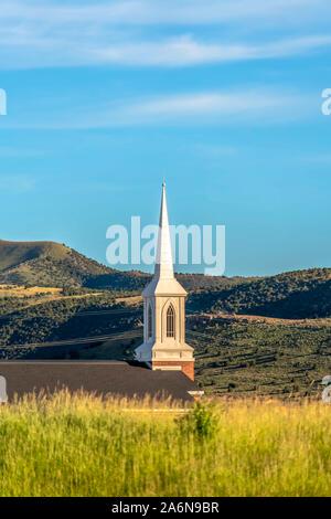 Clocher sur le toit et d'une église avec vue sur la montagne et le fond de ciel bleu pâle Banque D'Images