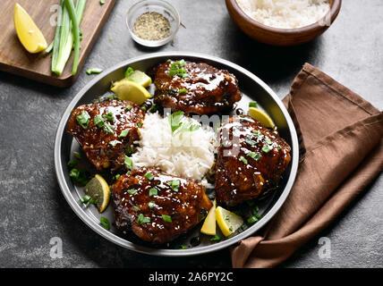 Close up de miel sucré et épicé de cuisses de poulet grillé avec du riz sur pierre sombre tableau. Une cuisine savoureuse dans un style asiatique. Banque D'Images
