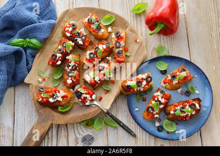 Bruschetta grecque chaleureuse: de petites tranches de pain pita avec du fromage feta, olives noires, poivrons rouges et basilic, servi en apéritif