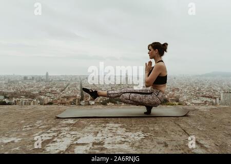 Young woman practicing yoga, asana, un pied sur le sol.