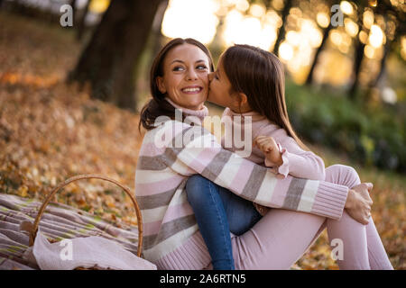 Embrassant sa mère est fille de l'automne dans le parc.