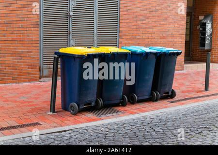 Conteneurs à ordures en plastique de différentes couleurs avec couvercles pour le tri de déchets respectueuse de l'environnement ou pour le recyclage des sacs en plastique pour la corbeille pleine Banque D'Images