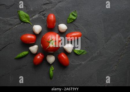 Pizza mozzarella ingrédients traditionnels italiens, de salami, de tomates et de feuilles de basilic composé dans une forme de fleurs sur fond noir pierre naturelle. Banque D'Images