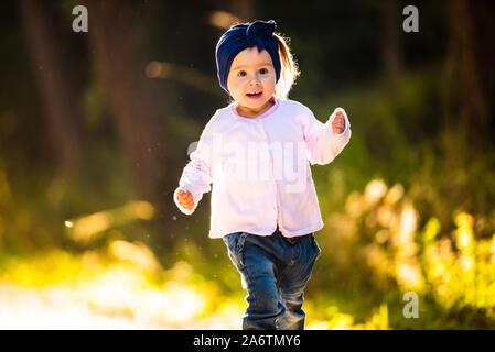 2 ans bébé fille courir en forêt vers la caméra. avec happy expression sur son visage Banque D'Images
