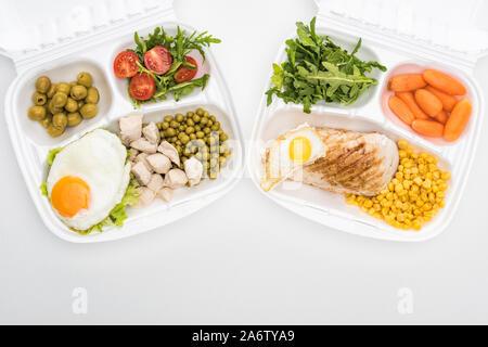 Vue de dessus d'eco forfaits avec roquette, légumes, viande, œufs frits et salade verte sur fond blanc Banque D'Images