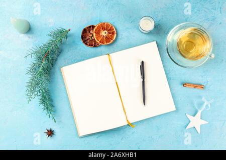 Résolutions pour la nouvelle année, télévision top shot laïcs avec copyspace, sur un fond bleu avec des décorations de Noël et thé chaud Banque D'Images