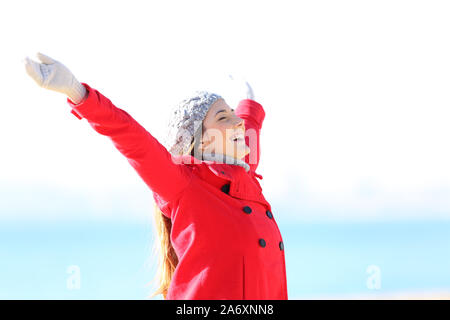 Femme en rouge excité raising arms célébrant l'hiver debout sur la plage