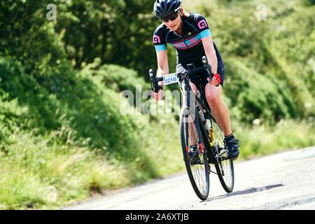 ROTHBURY, Newcastle upon Tyne, England, UK - Juillet 06, 2019: A female cyclist riding vite le long d'un chemin de campagne à l'événement de course cyclone Newcastle Banque D'Images