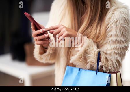 Les femmes adultes dans les boutiques de vêtements en boutique, à l'automne et using smartphone
