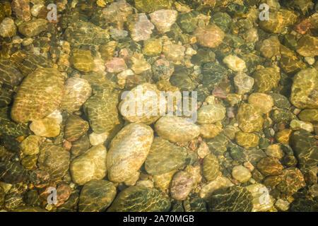 Les rayons du soleil reflétant sur des pierres sous l'eau Banque D'Images