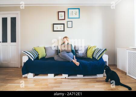 Jeune blond Caucasian woman doing shoppings en ligne sur le canapé à la maison, regardant un écran d'ordinateur portable et de sourire. Chat noir sur l'avant-plan