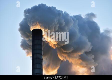 Cheminée industrielle fumeurs, contre un ciel clair au coucher du soleil. Banque D'Images