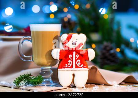 Délicieux cappuccino tasse en verre avec noël ours gingerbread cookie. lucioles et branches de l'arrière-plan Banque D'Images