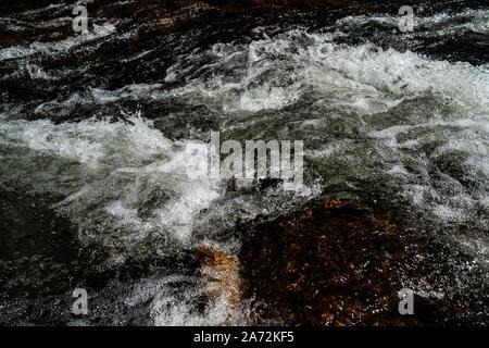 Close up de l'eau qui coule sur les rochers, dans une petite rivière, lumineux Victoria Australie Banque D'Images