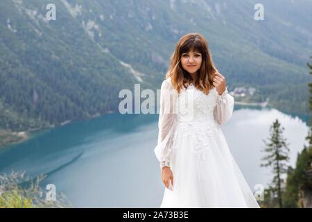 Jolie jeune femme passer du temps dans les montagnes près du lac. La mariée se présente. Banque D'Images