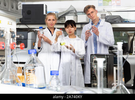 Adulte de sexe masculin et les femmes scientifiques en blouse blanche qui pose au laboratoire de biochimie Banque D'Images