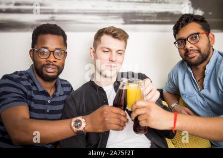 Closeup portrait de trois beaux mâles multi ethnic friends en tenues décontractées tintement des bouteilles de boissons smiling at camera. Les gens, hommes, leis Banque D'Images